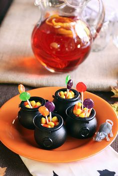 Adorable little black plastic cauldrons used to house Halloween sweets. #candy #decor #party #kids #food #cauldron #Halloween #treats #candy_corn #lollipops #autumn #fall