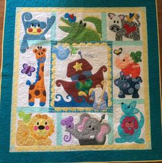 """""""Noah & Friends"""" patterns from Kookaburra Cottage.  Quilted block by block, using fusible batting.  Very big project, very fun to make.  Noah's ark themed fabric on the back. Made for a good friend's grandnephew."""