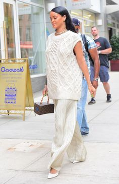 Rihannawears a cream sleeveless sweater, wide leg pin-striped pants, pointed-toe heels and a box bag by Louis Vuitton while out in NYC.