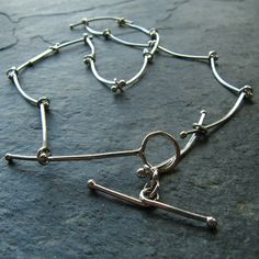 Silver Handmade Chain Stick Modern Necklace by mylenefoster I made this stick necklace with fine silver wire (.999). I balled the ends and connected it with rings. I also made the matching toggle clasp which has an extended handle. Purely unique and exclusive. Fine silver is a bit softer than sterling silver so the sticks will give some when bent with force.