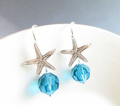 These ocean inspired earrings are handcrafted with 8mm aqua Swarovski crystal dangling from intricately detailed sterling silver starfish ear