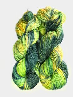 Hand dyed yarn in shades of bright apple green, a darker green with a hint of blue, yellow, and a touch of orange. The skein on the left of the