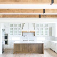 My ideal kitchen - white backsplash, white countertops, exposed wood beams. I'd keep the upper cabinets white and make the lower cabinets/island a darker shade (dark gray/taupe)