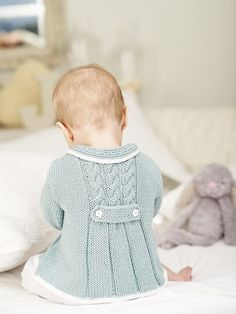 Knitting Patterns by King Cole, from King Cole Baby Book 5, offers this Vintage Sunday Coat pattern for babies and toddlers, shown in pale blue-gray.  Pinned by Nancy Lee Moran in 2016 from the online knitting and crocheting shop of Laughing Hens #knitting #crocheting #baby
