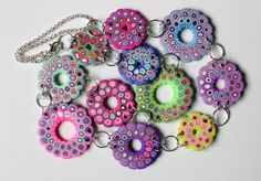 Necklace consisting of eleven polymer clay reversible pieces in a variety of sizes (between 1 4/5 and 1 1/5; 5/64 thickness), linked to each