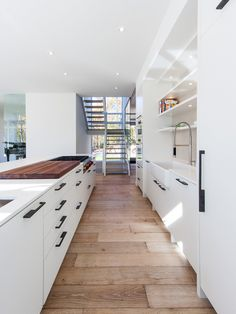 A Chic Kitchen Hallway With Minimalist White Kitchen Cabinet And Kitchen Island With Wooden Flooring And