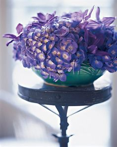 Martha's Tips: Create a study in color with different flowers in shades of the same hue. Hydrangeas and clematis in purple tones look unified yet diverse. The aqua-colored McCoy bowl peeking out is a bright surprise.