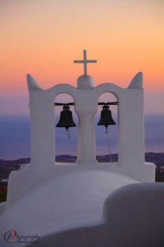 Church Bells and Cross during the Sunset Time in Pyrgos, Santorini Island, Greece