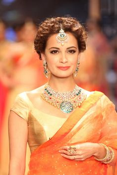 Kundan jewelry with emerald tones compliments this gold blouse-orange sheer saree. Middle partition hair bun look keep it chic. I would suggest this for post-haldi ceremony, muun dikhai, pre-wedding dinners, Temple visits, and post wedding pooja. If the wedding is in the evening, this is a apt afternoon look for the bride: family lunch, arrival at the ceremony venue, and shagun ritual. To save time, one can keep the same hairdo between multiple saree changes. ~Sayali
