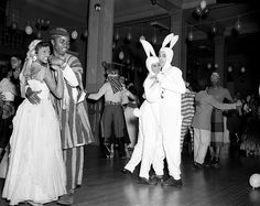 Couples dancing in costume during Omega Mardi Gras, sponsored by Howard University's Omega Psi Phi Fraternity, 1930s