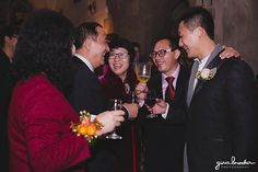 A candid photograph of a groom laughing with his family during the cocktail hour of their Hammond Castle Wedding in Gloucester, Massachusetts Gina Brocker Photography