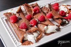 This recipe for healthy chocolate crepes tastes delicious. It's filled with a greek yogurt and cream mixture and topped with shaved chocolate and berries.