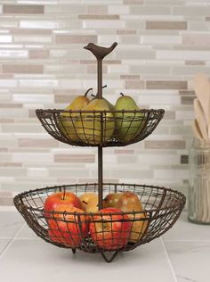"Our two-tiered fruit bowl stand features an oh, so sweet song bird atop the center stem! Measuring 15½"" tall, and 12"" across the bottom bowl, this wire bowl matches our General Store Multi-bin Racks!"