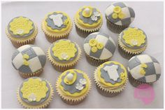 Baby shower cupcakes with a unisex theme in yellow, white and grey and decorated with blankets, vests, buttons and dummies. x