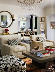 Chic, eclectic living room design with tan burlap club chairs, white & black ikat pillows, espresso modern cocktail table, black convex mirror and crystal chandelier.