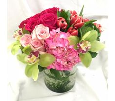 An echanting bouquet modern in styling, compact in a leaf lined cylinder with all flowers in shades of lavender, red, pink, white and green.   Measures approx 15x15