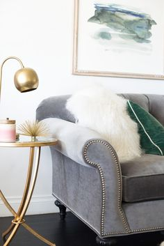 brass table lamp with gray tufted sofa