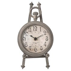 """ORWELL TABLE CLOCK $29.95 WAS $36.00 Quantity ADD TO SHOPPING BAG» Pay $9.95 today & get 30 days of free standard shipping DETAILS  Accent a vintaged vignette with this antique-inspired table clock, showcasing a pocket watch silhouette and easel-style stand. Product:Table clock Construction Material:Pewter Color:Distressed gray Features: Pocket watch silhouette Easel-style stand included Accommodates:Batteries - not included Dimensions:8.625"""" H x 4.75"""" W x 4.75"""" D"""