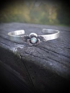 A hand fabricated, polished flower that frames a Lab Opal. It sits sweetly on a Sterling cuff with a brushed finish. Handcrafted Jewelry, Cuff Bracelets, Opal, Silver Rings, Jewelry Making, Jewels, Sterling Silver, Michigan, Frames