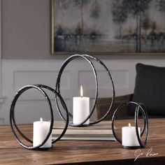 Set of Three Circular Black Iron Candle Holders Aged Black Curved Metal With Silver Highlights And Distressed White Candles. Sizes: Sm-7x7x5, Med-10x10x5, Lg-13x13x5Set of Three Circular Black Iron Candle Holders