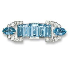 AN AQUAMARINE AND DIAMOND BROOCH, BY CARTIER. Designed as an arched graduated line of rectangular-shaped aquamarines to the circular-cut diamond and fancy-cut aquamarine buckle-shaped terminals, circa 1945, 5.4 cm wide. Signed Cartier, London