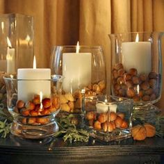simple candles in a variety of glass vases/hurricanes with chestnuts for thanksgiving/fall. then for xmas can switch nuts for something christmasy