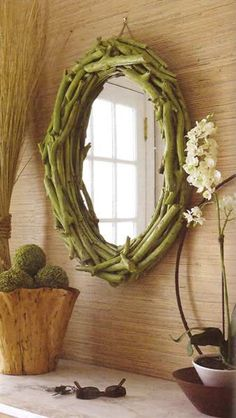 Need some budget decor ideas for mirrors? How about buying a thrift store mirror and affixing freshly painted twigs to the frame?