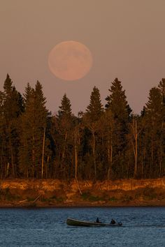 Full moon rising over Butler Island in the Moose River across from Moosonee, Ontario on 2012 August 31st. This is the second full moon of August so it is sometimes called the Blue Moon. Canoe on the Moose River visible at bottom of image.