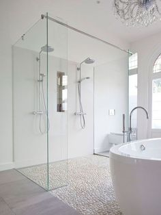 Shower floor - Modern bathroom features a crystal chandelier free standing acrylic tub a mix of marble tile and pebble floor and a double shower with custom made glass panels.