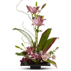 Pink Asiatic lilies rise up from a square design block holding a mix of cymbidium orchids, spray roses and accent blooms and greenery.