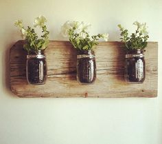 Decorating your home with plants brings the outdoors in! Try these creative ways to make DIY recycled planters! With mason jars, books and even chairs! Mason Jar Sconce, Mason Jar Planter, Mason Jar Vases, Glass Jars, Hanging Wall Vase, Diy Hanging, Wall Vases, Wall Planters, Hanging Jars
