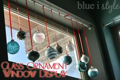 A glass ornament window display -  a great way to keep fragile ornaments safely out of the reach of little hands, and it looks beautiful from both inside and outside of the house {blue i style}