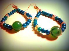 Orecchini a goccia realizzati con perle in acrilico e metallo. Al centro un perla in pietra naturale.