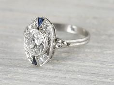VintageArt Deco engagement ring made in platinum and centered with an approximate 1.15 carat EGL certified old European cut diamond with J color and SI1 clarity. Accented by single cut diamonds and two triangle shaped sapphires.Circa 1920 The setting has an oval shape which emphasizes the lovely center diamond. Sits very low on the finger.Learn more about Art Deco rings Diamond and gold mining has caused devastation in areassuch as Africa, wreaking havoc on delicate ecosystems and…