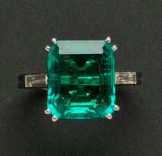 Fine Colombian Emerald Ring, Boucheron, Paris, c. 1920s, prong-set with and emerald-cut emerald measuring approx. 11.53 x 9.89 x 4.61 mm, and weighing 4.06 cts., flanked by diamond baguettes, platinum mount, no. X3057, size 5 1/4, signed.