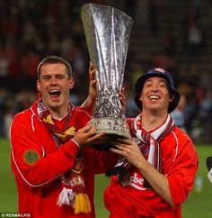 Jamie Carragher (left) lifts the UEFA Cup with Robbie Fowler (right) after winning the tournament in 2001