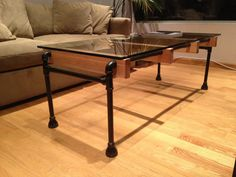 A modern industrial coffee table made of black steel pipe, lightly stained doug fir wood, and 1/2 thick tempered glass. The dimensions for the