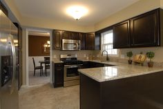 My idea of a perfect kitchen=dark cabinets, light colored counters and stainless appliances