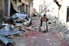 Ein Junge schiebt einen Rollstuhl durch das Viertel Maschatije in Aleppo. Mehr...