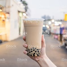 A young woman is holding a plastic cup of brown sugar bubble milk tea at a night market in Taiwan, Taiwan delicacy, close up. Tea Restaurant, Bubble Milk Tea, Close Up Photos, Young Women, Taiwan, Brown Sugar, Glass Of Milk, Hold On, Bubbles