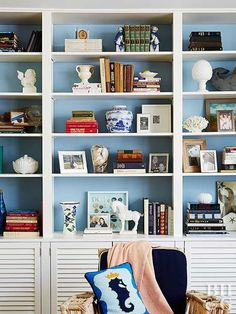 Carry your color scheme onto your bookshelf to give the room a sense of unity. Here, accessories on the shelves match the light blue of a nearby throw pillow. Storage cabinets conceal items like toys and movies that you may not want out in the open.