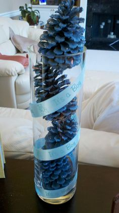 Cute and easy idea for a baby boy baby shower! Spray paint pine cones to fill a vase and then spiral a ribbon around it! Easy centerpiece!