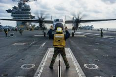 """PHILIPPINE SEA (Dec. 1, 2013) Aviation Boatswain's Mate 3rd Class Israel Rodriguez, from Brownsville, Texas, directs a C-2A Greyhound from the """"Providers"""" of Fleet Logistics Support Squadron (VRC) 30, Det. 5, on the flight deck of the U.S. Navy's forward-deployed aircraft carrier USS George Washington (CVN 73) during Carrier Air Wing (CVW) 5's fly-off. (U.S. Navy photo by Mass Communication Specialist 3rd Class Ricardo R. Guzman/RELEASED)"""