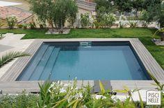 Une piscine entourée de verdure.