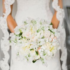 The Bouquet Southern Blooms created the bridal bouquet out of white- and blush-colored roses and peonies.