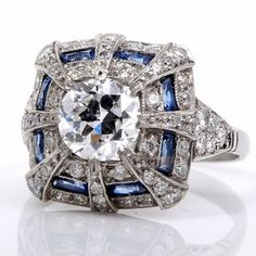 Antique 2.92ct Diamond Sapphire Platinum Engagement Ring.        This exquisite antique diamond sapphire engagement ring is beautifully handcrafted in solid platinum. This lovely ring is centered with 1 genuine round European diamond approx 1.17ct, F color, SI1 clarity, bezel set. Also displayed are some 58 genuine round diamonds approx 1.00ct, I color, VS clarity, and 8 genuine french baguette cut sapphires approx 0.75ct, channel set.  Via Dover Jewelry.