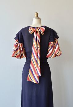Vintage 1930s navy blue tucked rayon dress with slight V neckline, double ruffled sleeves, striped silk back tie at the collar, striped silk balloon sleeves and side snap closures.  --- M E A S U R E M E N T S ---  fits like: small bust: 33 waist: 27 hip: 32 length: 47 brand/maker: n/a condition: this dress looks so great but there is damage on the sleeves, small tears throughout both of them, it can still be worn, but the damage should be taken into consideration  to ensure a good ...