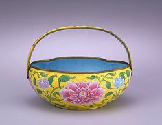 Painted enamel crabapple flower basket, Qing Dynasty.  The yellow ground of this flower basket is a distinct sign of the late Kangxi period of the early Qing Dynasty, when the painted enamel arts reached their peak. The pink crabapple flowers, contrasted with small blue lotuses, were painted on the basket to signal a wish for wealth and harmony. The basket, made for imperial use, is one of the representative painted enamel works created under the direction of several European artists.