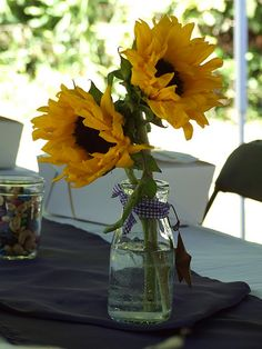 """From our own Newman Wedding """"Shindig"""" Picnic Reception: Sunflowers in vintage milk jars, tied with blue gingham ribbon and adorned with tin stars. Blue and blue gingham table runners were used. """"To Go"""" boxes were tied with raffia."""