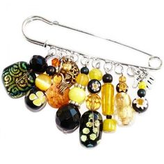 Grote speld broche met luxe glaskralen in goud, geel en zwarte kleuren. Handgemaakte kiltspeld met glaskralen uit eigen atelier.